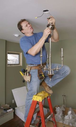 man changing chandelier