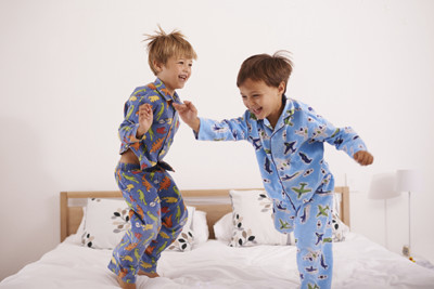 kids in pajamas jumping on bed